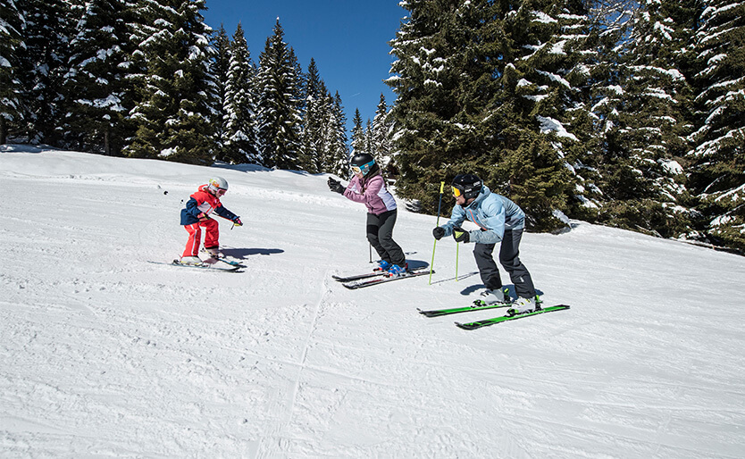 kids skiing and family